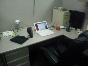 Photo of an empty desk with a laptop, computer speakers, and a coffee mug.