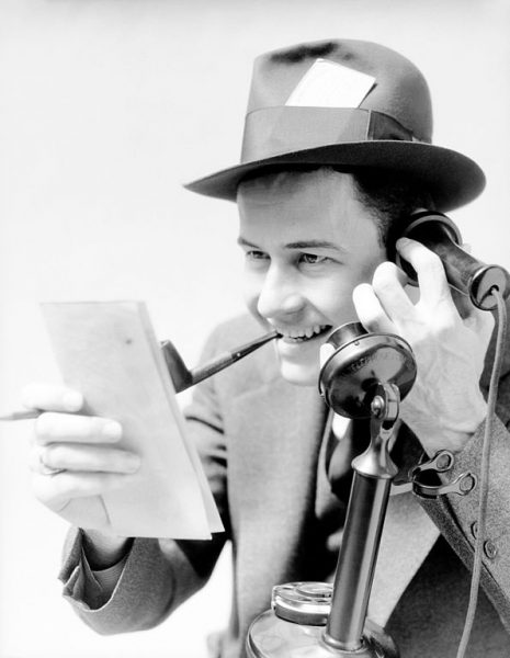 Black and white image of a journalist. This is how I imagine old-timey sportwriters looked, pipe clenched in his teeth, holding an old style phone.