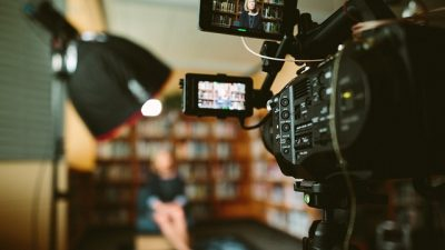 A video camera recording a woman against a set of bookshelves. Video is an important part of any storytelling campaign these days.